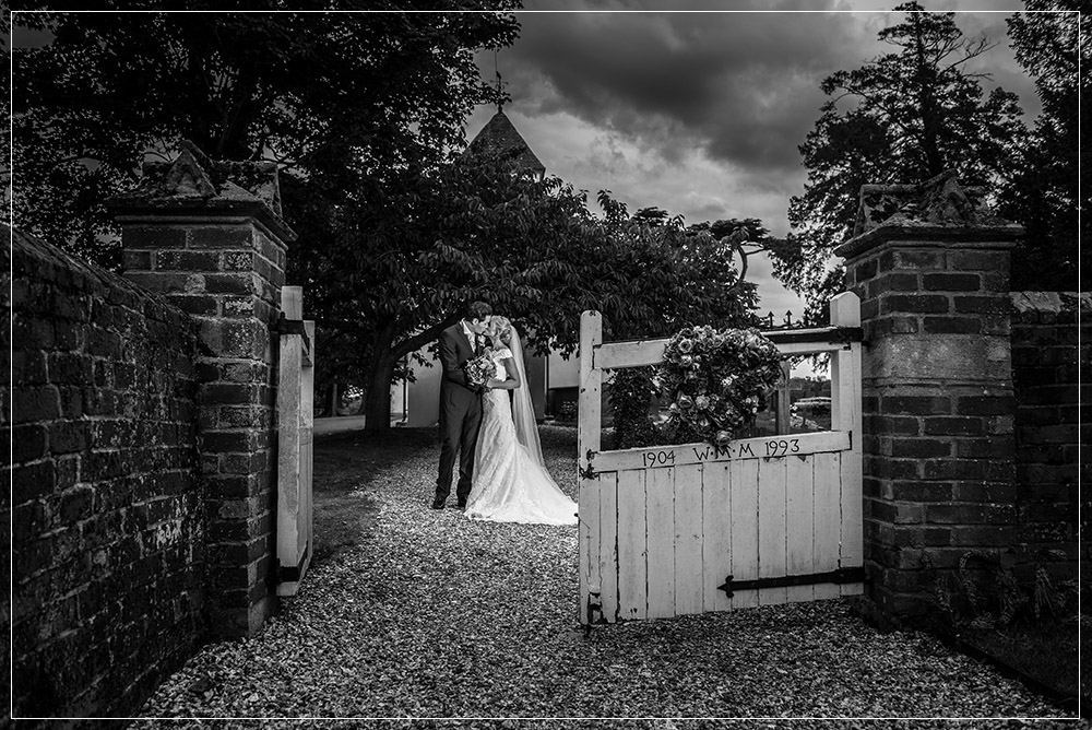 bride and groom black and white in gate by church